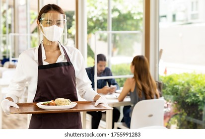 Portrait attractive asian waitress wear face mask and face shield holding food tray to serving meal to customer with custome in background. New normal restaurant concept.