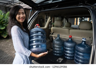 portrait of attractive asian woman carrying a gallon of water and put into her car trunk