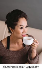 Portrait of attractive Asian woman drinking tea