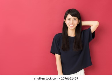 portrait of attractive asian woman isolated on red background