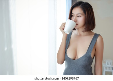 portrait of attractive and asian woman in sexy dress standing beside window and drinking coffee in the morning with relaxation