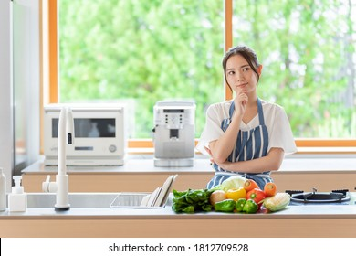 portrait of attractive asian woman thinking at kitchen