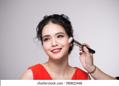 Portrait of attractive asian young adult woman applying blusher