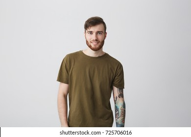 Portrait of attractive bearded caucasian man with tattoo on arm and stylish hairstyle wearing casual green t-shirt, looking in camera with happy and satisfied expression. Positive emotions.
