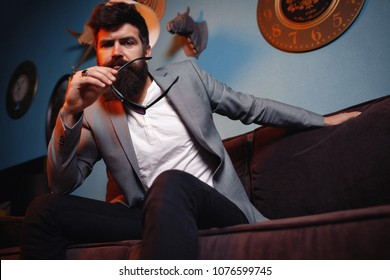 Portrait of attractive bearded man in business suit and sunglasses sitting in couch. Successful businessman dreaming about future, enjoys luxury. Male waiting too long for business meeting to start