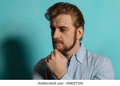 Portrait of an attractive bearded man with hair in the style of rockabilly in a striped shirt. As for the arm beard blue wall