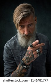 Portrait of an attractive bearded man in a studio, who is pointing with his finger to you
