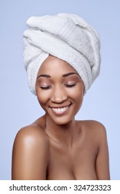 Portrait of attractive beautiful black african woman with towel wrapped around her hair, beauty skincare cosmetics concept