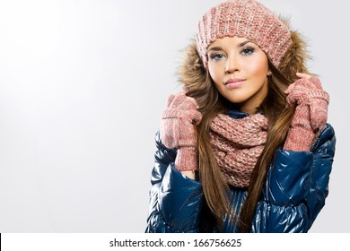 Portrait of attractive beautiful young woman wearing gloves, scarf and winter cap, white background