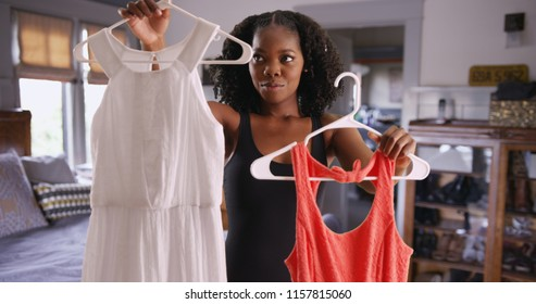 Portrait of attractive black woman deciding what dress to wear