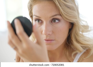 Portrait of attractive blond woman putting makeup on