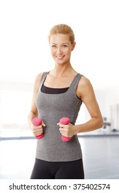Portrait of an attractive blond woman working out with weights while standing at gym.