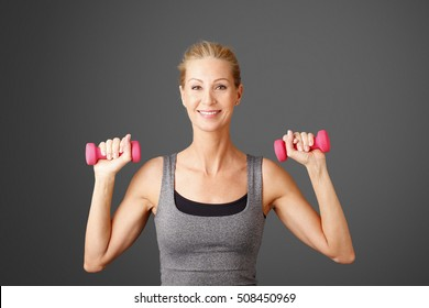 Portrait of an attractive blond woman working out with weights while standing against isolated background.