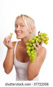 Portrait of a attractive blonde eating grapes