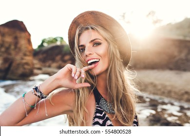 Portrait of attractive blonde girl with long hair posing on rocky beach on sunset background. She wears bikini, hat. She holds finger on lips and looks to the camera.