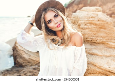Portrait of attractive blonde girl with long hair posing on deserted beach. She wears white shirt, hat, ornamentation. She is smiling to the camera.