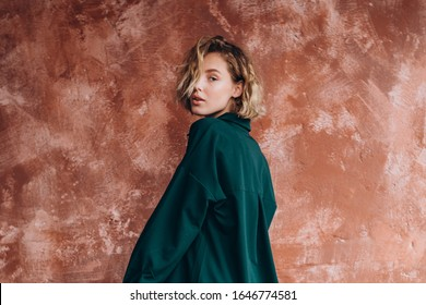 Portrait of an attractive blonde woman poses for the advertisement of a women's clothing store dressed in a dark green pantsuit with a shirt
