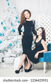 Portrait of attractive brunette and brown-haired girls. Christmas background.