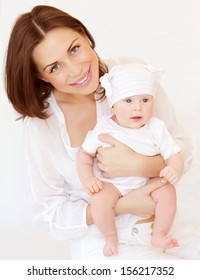 Portrait of attractive brunette mother carry cute baby girl in hands, at home, happy motherhood, young family, love concept