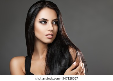 Portrait attractive brunette on a gray background. Beautiful dark hair. Girl looking away