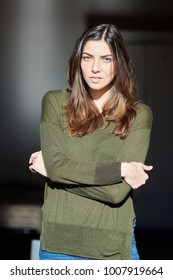 Portrait of attractive brunette woman in casual khaki pullover with crossed arms looking at camera in sunlight.