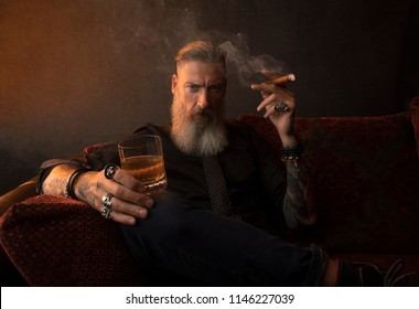 Portrait of an attractive business man with a cigar and a glass of whiskey in a dark room