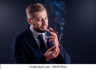 Portrait of an attractive business man with a cigar in black background studio