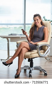 Portrait of attractive business woman sitting on armchair with smartphone in her hands