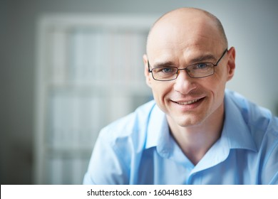 Portrait of attractive businessman in eyeglasses looking at camera