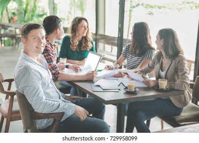 portrait of attractive businessman and his team during meeting in a coffee shop