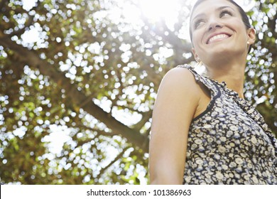 Portrait of an attractive businesswoman with foliage around her and sunlight coming through.
