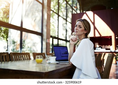 Portrait of an attractive businesswoman resting after on-line conference via laptop computer during her summer vacation, pretty Sweden female relaxing after working on net-book during coffee break