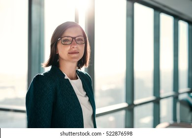 Portrait of an attractive businesswoman standing in front of windows in an office building overlooking the city