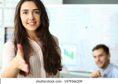 Portrait of attractive businesswoman standing in modern office and reaching arm to perform handshake with smart corporation partner. Biz meeting concept. Blurred background