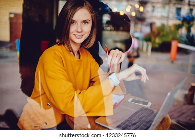 Portrait of attractive businesswoman with stylish short haircut smiling at camera while managing time on display of modern smartwatch sitting behind glass window of cafeteria with laptop computer