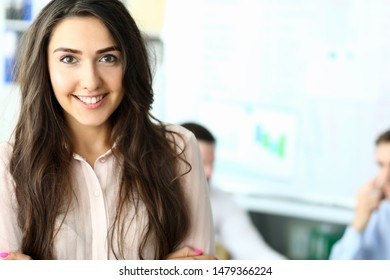 Portrait of attractive businesswoman working in modern office with joyful colleagues and discussing important topic. Pretty woman wearing trendy pink blouse. Biz meeting concept. Blurred background