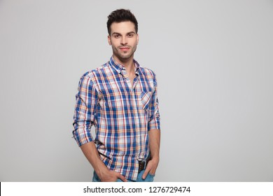 portrait of attractive casual man wearing a plaid shirt standing with hands in pockets on ;ight grey background