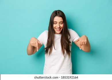 Portrait of attractive caucasian brunette girl in white t-shirt, looking and pointing fingers down, showing logo, standing over blue background