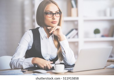 Portrait of attractive caucasian businesswoman in formal outfit and glasses sitting at office desk with laptop