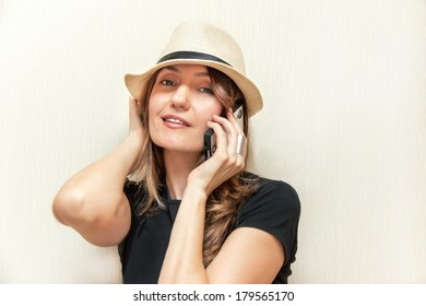 Portrait of attractive caucasian girl. Happy female is holding and  using mobile telephone. Young woman is smiling. Caucasian beautiful young girl. Pretty fashion model girl. Close up. Indoor.