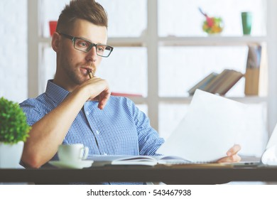 Portrait of attractive caucasian guy with document in hand at workplace