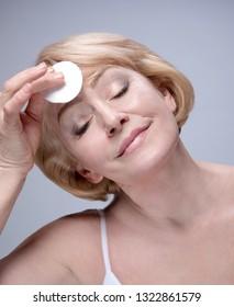 portrait of attractive  caucasian smiling mature woman blond studio shot face care cotton disc cleaning face