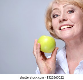 portrait of attractive  caucasian smiling mature woman blond studio shot with green apple