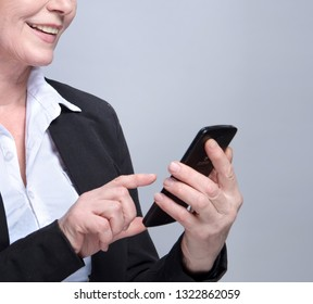 portrait of attractive  caucasian smiling old woman  studio shot looking at smartphone