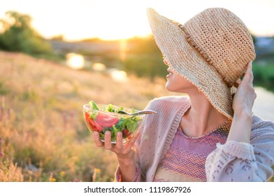 Portrait of attractive caucasian smiling woman eating salad with beautiful sunset sun on a meadow landscape