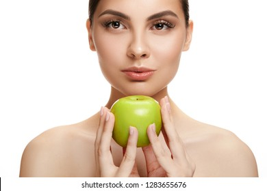 The portrait of attractive caucasian smiling woman isolated on white studio background with green apple fruits