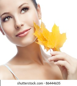 portrait of attractive  caucasian smiling woman isolated on white studio shot with yellow maple leaf looking up