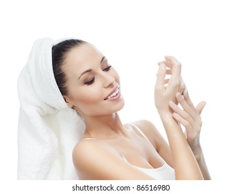 portrait of attractive  caucasian smiling woman isolated on white studio shot applying cream on her hands in towel on her head