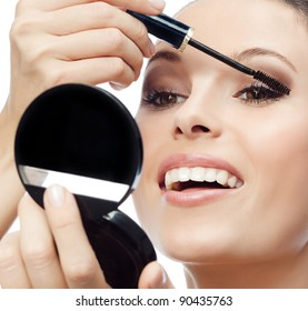 portrait of attractive  caucasian smiling woman isolated on white studio shot applying mascara