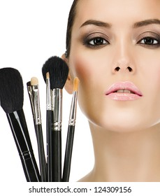 portrait of attractive  caucasian  woman brunette isolated on white studio shot closeup makeup brushes